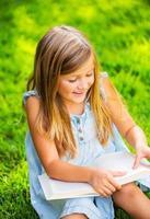schattig klein meisje leesboek buiten op gras foto