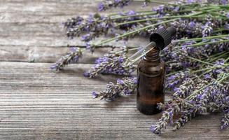 kruidenolie en lavendel bloemen boeket op houten achtergrond foto