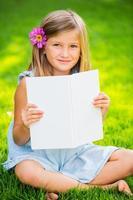 klein meisje leesboek buiten foto