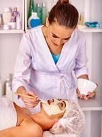 vrouw van middelbare leeftijd nemen gezichtsmassage in spa salon foto