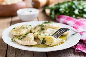 met aardappel gevulde varenyky op een witte plaat op houten tafel