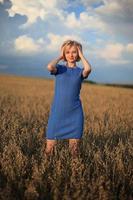 mooie lachende vrouw in een veld bij zonsondergang