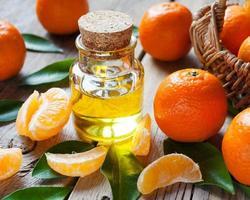 fles essentiële citrusolie en rijpe mandarijnen met bladeren foto