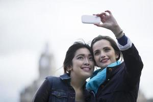 Kaukasische en Chinese vrienden nemen foto met telefoon.