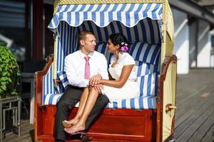 mooie Indiase vrouw en blanke man, in strandstoel. foto