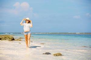jong mager Kaukasisch meisje bij het strand met blauwe hemel foto