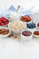 haver vlokken en verschillende ingrediënten voor het ontbijt op witte tafel foto