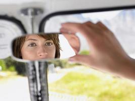 vrouw achteruitkijkspiegel in busje aanpassen