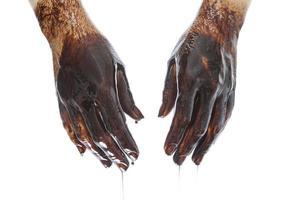 Kaukasische handen gekleurd met zwarte olie geïsoleerd op een witte achtergrond foto
