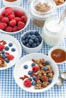 ontbijt met muesli, bessen, honing en yoghurt, bovenaanzicht foto