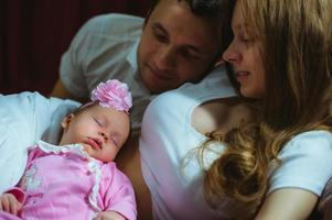 beeld van jonge Kaukasische familie binnen. vader, moeder en schattig foto