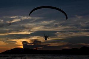 silhouet paramotor / paraglider vliegen in de lucht met seavie