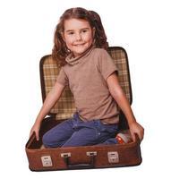 meisje baby brunette zitten in een koffer voor reizen geïsoleerd foto