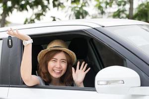Aziatisch meisje toont nieuwe autosleutel voor rijden om te reizen foto