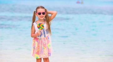 schattig klein meisje veel plezier met lolly op het strand foto