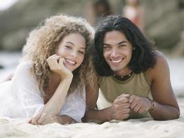 jong koppel liggend op het strand en glimlachen foto