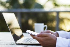 man aan het werk met een laptop en mobiele telefoon bij zonsopgang foto