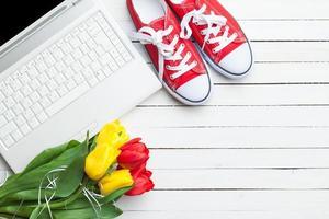 witte computer en boeket tulpen met gumshoes foto