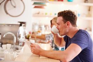 jonge man met behulp van tablet-computer in een café foto