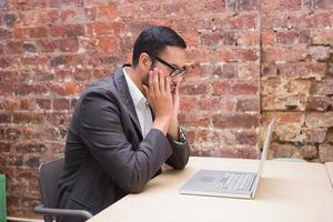 geconcentreerde zakenman die laptop met behulp van bij bureau foto