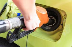 vrouwen houden brandstofpijp aan auto bij benzinestation foto