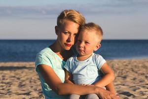 gelukkige familie rusten op het strand in de zomer
