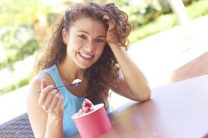 jonge vrouw die van bevroren yoghurt geniet foto