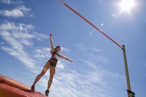 jonge vrouwelijke atleet die voorbereidingen treft om over bar te springen (lensflare) foto