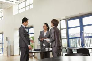drie mensen uit het bedrijfsleven bijeen in bedrijfscafetaria foto
