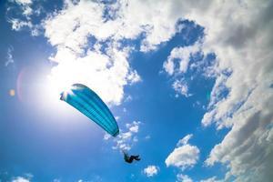 paraglider zweeft in een zonnige blauwe hemel
