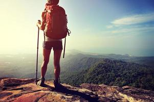 vrouw wandelaar geniet van het uitzicht op de bergtop klif foto