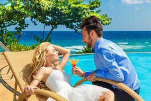 gelukkige bruid en bruidegom genieten van een cocktail oneindigheid bij het zwembad foto
