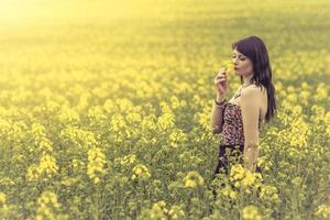 mooie vrouw in weide van gele bloemen die van bloem genieten foto