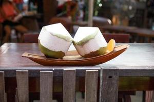 hak de toppen af en geniet van verfrissend kokoswater. foto