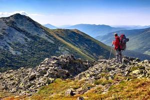 wandelaar met rugzak staande in de bergen en genieten van de v foto
