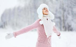 gelukkige vrouw genieten van besneeuwde winterweer in het bos