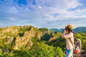 wandelaar vrouw met camera genieten van het uitzicht bij zonsopgang foto