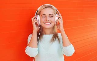 mooie jonge vrouw luistert en geniet van de muziek in de koptelefoon foto