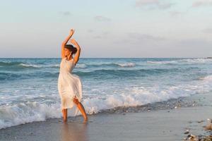 jonge vrouw geniet van een wandeling op het strand in de schemering.