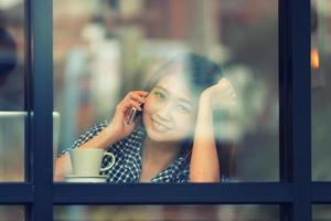 Azië glimlach vrouw praten telefoon in café en genieten van koffie foto