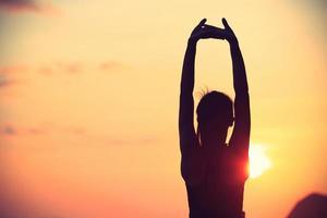gezonde fitness yoga vrouw armen strekken bij zonsopgang aan zee foto