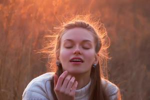 mooie jonge blonde vrouw dagdromen bij zonsondergang foto