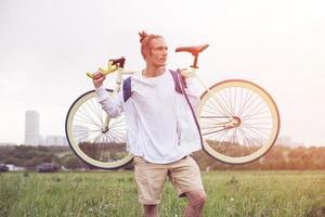 man in lege t-shirt staan met fiets