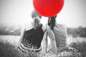 twee beste vriendinnen zittend op het gras foto