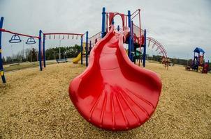 speeltuin met een rode glijbaan foto