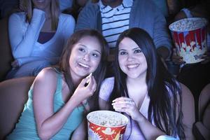 vrienden kijken naar film in de bioscoop foto