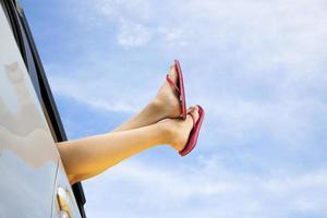 de benen van de jonge vrouw en het concept van de de zomerreis van de weg foto