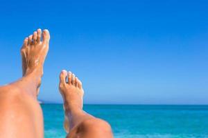 close-up van vrouwelijke benen achtergrond van de turquoise zee foto