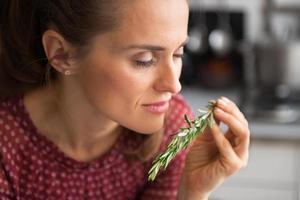 jonge huisvrouw genieten van verse rosmarinus