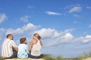 ouders en zoon genieten van uitzicht op het strand foto